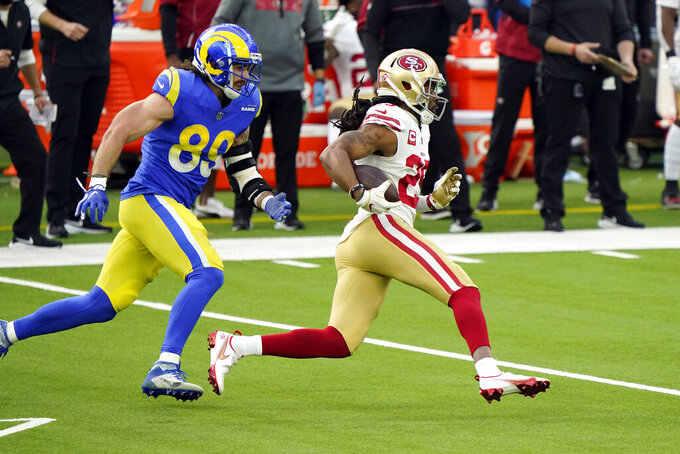 San Francisco 49ers cornerback Richard Sherman, right, runs back with an intercepted pass next to Los Angeles Rams tight end Tyler Higbee (89) during the first half of an NFL football game Sunday, Nov. 29, 2020, in Inglewood, Calif. (AP Photo/Alex Gallardo)