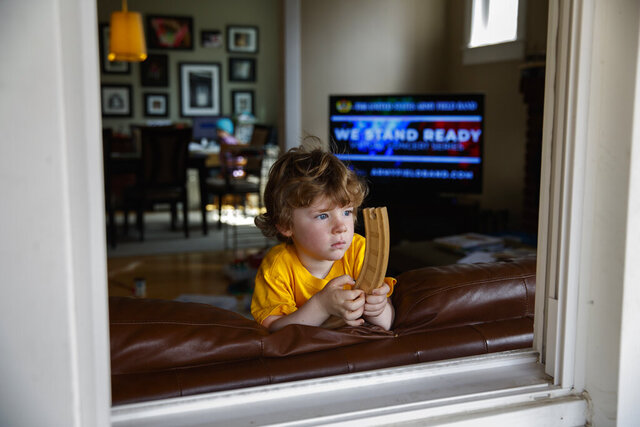 Ethan McIver, 4, son of U.S. Army Field Band member Sgt. Major Robert McIver, Jr., holds part of his toy train set as he looks out the window of his home in Catonsville, Md., Thursday, March 26, 2020. The family is staying home because of the coronavirus outbreak. Inside on the television the U.S. Army Field Band's daily