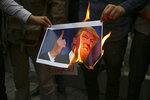 FILE - In this May 9, 2018, file photo, Iranian demonstrators burn a picture of the U.S. President Donald Trump during a protest in front of the former U.S. Embassy in Tehran, Iran. (AP Photo/Vahid Salemi, File)