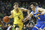 Oregon's Chris Duarte, left, drives to the basket against UCLA's Jaime Jaquez Jr. during the first half of an NCAA college basketball game in Eugene, Ore., Sunday, Jan. 26, 2020. (AP Photo/Chris Pietsch)