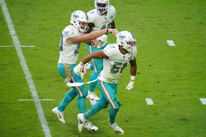 Miami Dolphins outside linebacker Kamu Grugier-Hill (51) celebrates a defensive stop with defensive end Shaq Lawson, left, and linebacker Sam Eguavoen (49) during the first half of an NFL football game against the Arizona Cardinals, Sunday, Nov. 8, 2020, in Glendale, Ariz. (AP Photo/Ross D. Franklin)