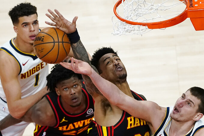 Denver Nuggets center Nikola Jokic (15) battles Atlanta Hawks' John Collins (20) and Cam Reddish (22) for a rebound during the first half of an NBA basketball game Sunday, Feb. 21, 2021, in Atlanta. (AP Photo/John Bazemore)