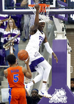 Florida guard KeVaughn Allen (5) watches as TCU forward Kouat Noi (12), of Australia, hangs on the rim after dunking in the first half of an NCAA college basketball game in Fort Worth, Texas, Saturday, Jan. 26, 2019. (AP Photo/Tony Gutierrez)