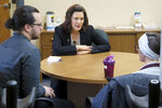 Michigan Gov. Gretchen Whitmer meets with Angela, right, and Ryne Weber at the Hope Network Neuro Rehabilitation campus Thursday, May 16, 2019, in East Lansing, Mich. Angela sustained a severe brain injury last August when a vehicle struck her while she was riding a bike. The Legislature is considering whether to end Michigan's unique requirement that drivers have unlimited medical benefits through their auto insurance policies. (AP Photo/David Eggert)
