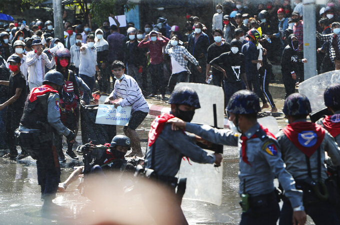 Protesters run after police fire warning-shots and use water cannons to disperse them during a protest in Mandalay, Myanmar on Tuesday, Feb. 9, 2021. Police cracked down Tuesday on the demonstrators protesting against Myanmar's military takeover who took to the streets in defiance of new protest bans. (AP Photo)