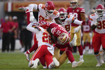 San Francisco 49ers running back Wayne Gallman II, middle, is tackled by Kansas City Chiefs defensive end Demone Harris (96) and defensive back Juan Thornhill, bottom left, during the first half of an NFL preseason football game in Santa Clara, Calif., Saturday, Aug. 14, 2021. (AP Photo/Tony Avelar)