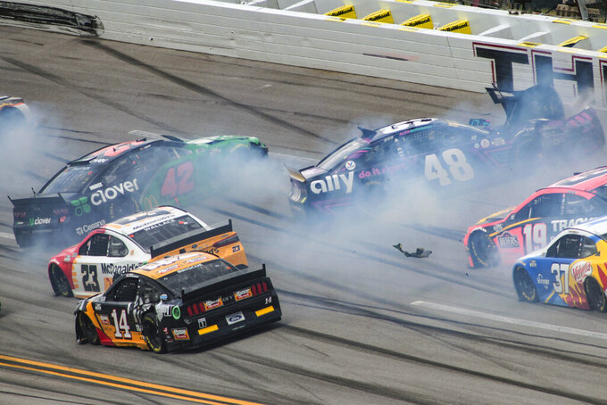 Ross Chastain (42) and Alex Bowman (48) get sideways during a NASCAR Cup series auto race Monday, Oct. 4, 2021, in Talladega, Ala. (AP Photo/Greg McWilliams)