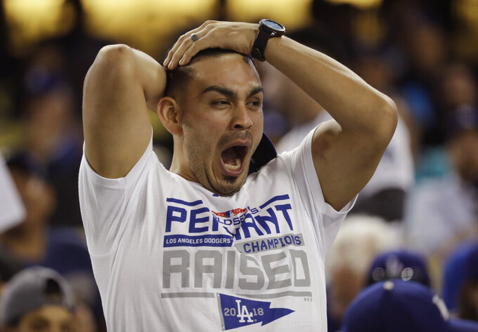 FILE - In this Oct. 26, 2018, file photo, a fan yawns before the start of the 17th inning in Game 3 of the World Series baseball game between the Boston Red Sox and Los Angeles Dodgers, in Los Angeles. Major League Baseball will start each extra inning this season by putting a runner on second base. This rule has been used since 2018 in the minor leagues, where it created more action and settled games sooner. (AP Photo/David J. Phillip, File)