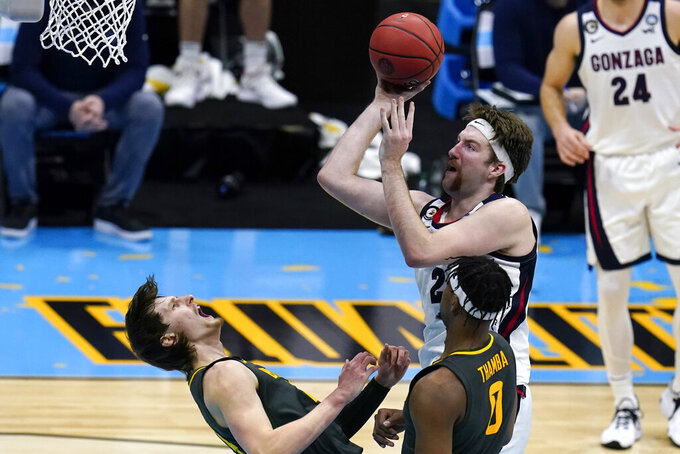 Baylor guard Matthew Mayer, left, draws a charging call on Gonzaga forward Drew Timme during the second half of the championship game in the men's Final Four NCAA college basketball tournament, Monday, April 5, 2021, at Lucas Oil Stadium in Indianapolis. (AP Photo/Michael Conroy)