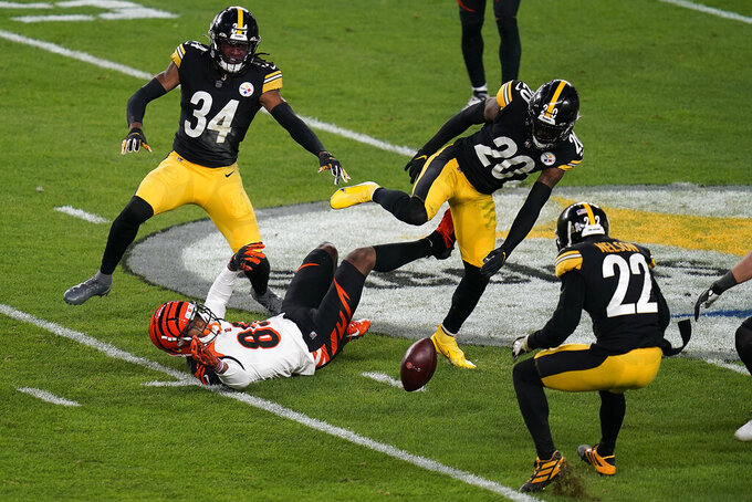 Cincinnati Bengals wide receiver Tee Higgins (85) fumbles the ball after taking a hit from Pittsburgh Steelers cornerback Cameron Sutton (20) during the first half of an NFL football game, Sunday, Nov. 15, 2020, in Pittsburgh. The ball was recovered by Steelers cornerback Steven Nelson (22). (AP Photo/Keith Srakocic)