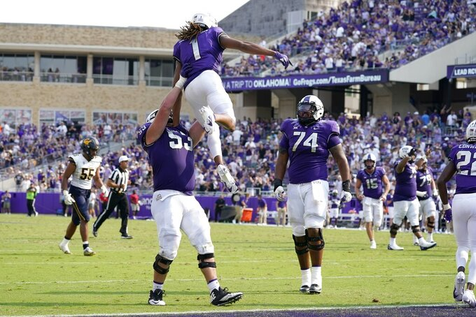 TCU guard John Lanz (53) and offensive tackle Andrew Coker (74) celebrate with wide receiver Quentin Johnston after Johnston caught a touchdown pass in the second half of an NCAA college football game against California in Fort Worth, Texas, Saturday, Sept. 11, 2021. (AP Photo/Tony Gutierrez)