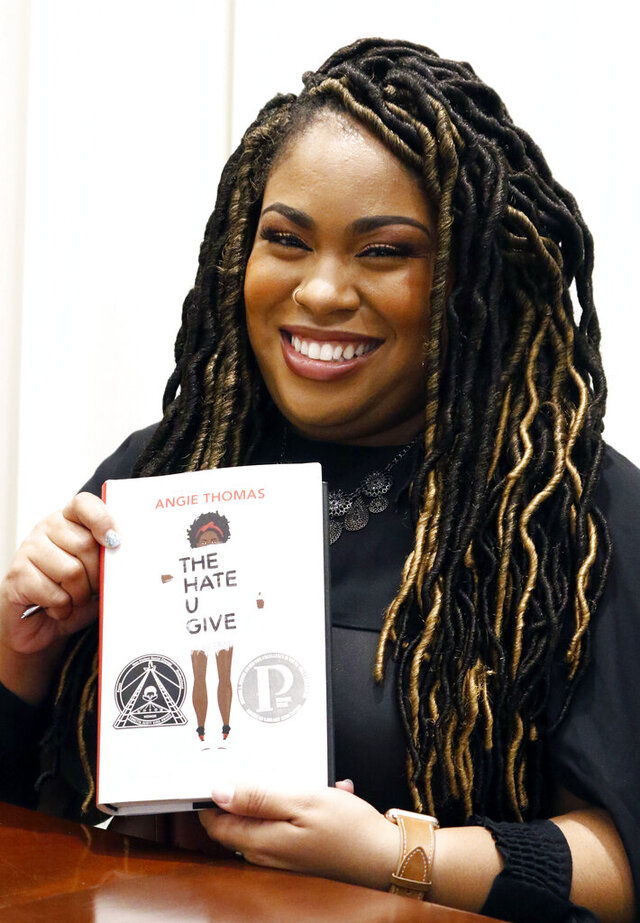 FILE - In this Oct. 10, 2018 photograph, author Angie Thomas holds a copy of her novel,