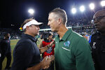 Tulane coach Willie Fritz and Houston coach Dana Holgorsen, left, greet each other after an NCAA college football game in New Orleans, Thursday, Sept. 19, 2019. Tulane won 38-31. (AP Photo/Gerald Herbert)