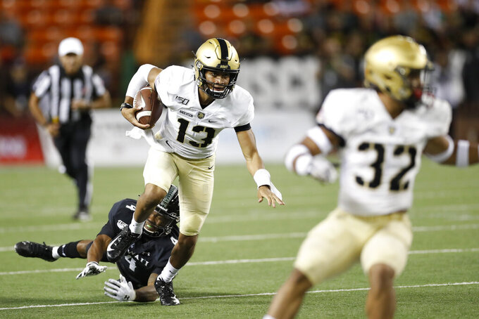 Army quarterback Christian Anderson (13) gets away from Hawaii defensive back Rojesterman Farris II (4) during the second half of an NCAA college football game Saturday, Nov. 30, 2019 in Honolulu. (AP Photo/Marco Garcia)