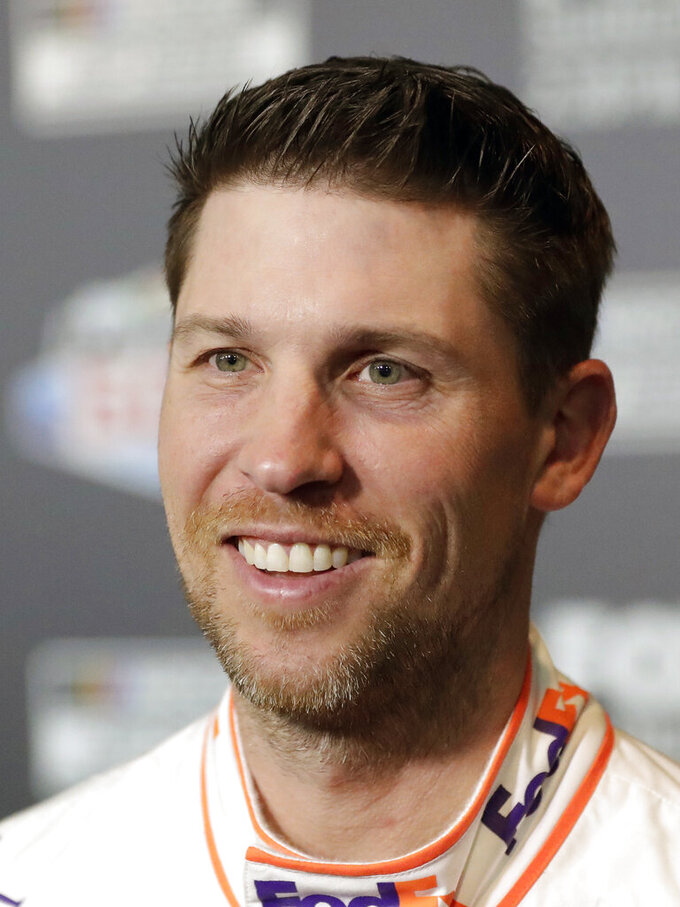 Denny Hamlin smiles during NASCAR Daytona 500 auto racing media day at Daytona International Speedway, Wednesday, Feb. 12, 2020, in Daytona Beach, Fla. Picking the car number for Michael Jordan's new NASCAR team was a slam dunk: Bubba Wallace will drive the No. 23 car when the team makes its debut next season. Jordan and Hamlin announced last month they had formed a NASCAR team with Bubba Wallace as the driver. (AP Photo/John Raoux)