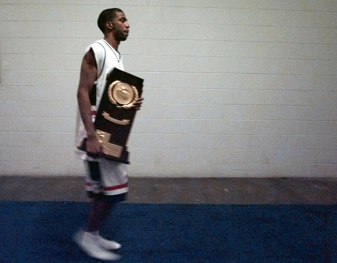 FILE - In this March 29, 1999, file photo, Connecticut's Richard Hamilton carries the NCAA college basketball championship trophy after participating in a news conference following the Final Four championship game at Tropicana Field in St. Petersburg, Fla. UConn defeated Duke 77-74. (AP Photo/Ed Reinke, File)