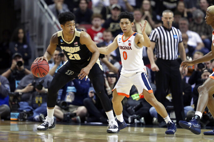 Purdue's Nojel Eastern (20) is defended by Virginia's Kihei Clark (0) during the first half of the men's NCAA Tournament college basketball South Regional final game, Saturday, March 30, 2019, in Louisville, Ky. (AP Photo/Michael Conroy)