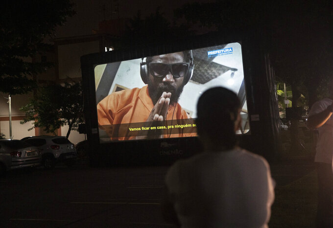A woman watches a short film on a giant screen in Rio de Janeiro, Brazil, Wednesday, May 13, 2020. Cinema from the windows is the name of a Rio City Hall initiative to bring the movie theater to people in quarantine at home due to the coronavirus pandemic. (AP Photo/Silvia Izquierdo)