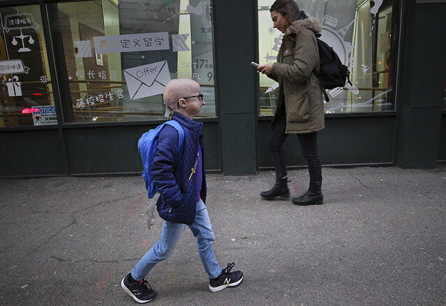 In this Feb. 12, 2019 photo, Meghan Waldron walks down the street in Boston. Waldron is a student at Emerson College with progeria, one of the world's rarest diseases. The first treatment has been approved for progeria, Friday, Nov. 20, 2020.  The U.S. Food and Drug Administration on Friday approved Zokinvy which was shown in testing to extend patients' lives by 2 ½ years on average.  (Suzanne Kreiter/The Boston Globe via AP)