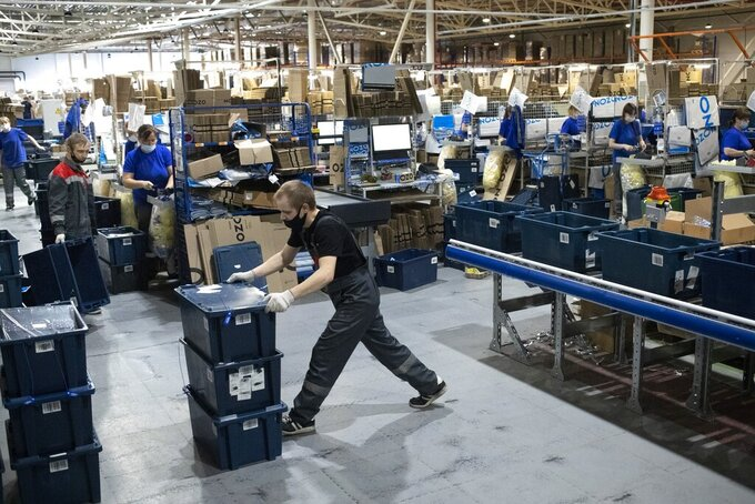 Employees work at Ozon, a major Russian e-commerce platform similar to Amazon, in Moscow, Russia, Thursday, March 25, 2021. Ozon saw its sales jump almost 2.5 times last year, the company's communications director Maria Zaikina said.  (AP Photo/Pavel Golovkin)