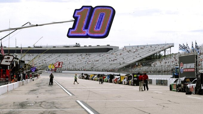 Fans sit socially distanced due to the coronavirus pandemic in the grandstand, rear, as a sign hangs over the pit location for driver Aric Almirola (10) before a NASCAR Cup Series auto race, Sunday, Aug. 2, 2020, at the New Hampshire Motor Speedway in Loudon, N.H. (AP Photo/Charles Krupa)