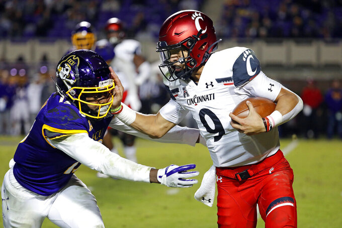 Cincinnati's Desmond Ridder (9) tries to break a tackle by East Carolina's Davondre Robinson (13) during the second half of an NCAA college football game in Greenville, N.C., Saturday, Nov. 2, 2019. (AP Photo/Karl B DeBlaker)