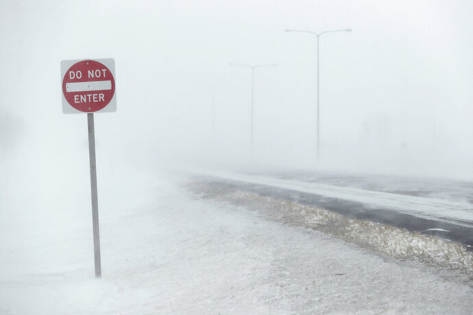 In this Wednesday, Feb. 12, 2020, photo, the driving lanes of U.S. Highway 281 north of Aberdeen, S.D., near Aberdeen Health and Rehab, were hard to see in the morning as high winds and blowing snow created blizzard and near white out conditions. (John Davis/Aberdeen American News via AP)