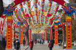 People wearing face masks walk under a canopy decorated with spinning colored fans for a canceled Lunar New Year temple fair at Longtan Park in Beijing, Saturday, Jan. 25, 2020. China's most festive holiday began in the shadow of a worrying new virus Saturday as the death toll surpassed 40, an unprecedented lockdown kept 36 million people from traveling and authorities canceled a host of Lunar New Year events. (AP Photo/Mark Schiefelbein)