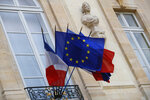 FILE - In this Monday, Dec. 10, 2018 file picture European and French flags are flapping at the Elysee Palace in Paris, during a meeting with French President Emmanuel Macron and local, national political leaders, unions, business leaders and others to hear their concerns after four weeks of protests. French Prime Minister Edouard Philippe announced Thursday that the government will start hiring 600 extra government employees including customs agents to handle cross-border trade and security. (AP Photo/Francois Mori, File)