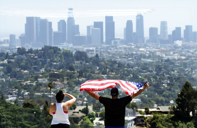 FILE - In this May 15, 2020, file photo, a couple salute the United States Air Force Thunderbirds who fly over downtown Los Angeles to honor frontline COVID-19 responders at Griffith Park in Los Angeles. (AP Photo/Chris Pizzello, File)