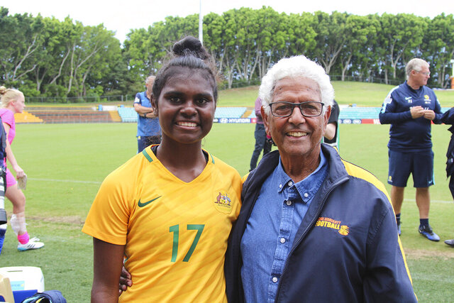 In this photo released by the Moriarty Foundation, Shadeene Evans, left, stands with John Moriarty at her debut for Australia's Young Matilda's under-20 national women's soccer team on March 16, 2018, in Sydney, Australia. With the support of the Moriarty Foundation, Evans went from playing for fun with her mates in the tropics of the Top End to studying at an elite sports high school in urban Sydney, catching the attention of the national women's coach, and making her way into Australia's top-flight women's league with Sydney FC. (Moriarty Foundation via AP)
