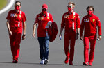 Ferrari driver Sebastian Vettel of Germany, third from right, inspects the track with team members ahead of the British Formula One Grand Prix at Silverstone circuit, Silverstone, England, Thursday, July 30, 2020.(AP Photo/Frank Augstein)