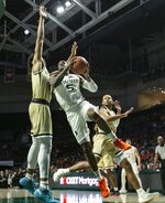 Miami guard Zach Johnson (5)  drives to the basket against the Georgia Tech defense during an NCAA college basketball game in Coral Gables, Fla., on Saturday, Feb. 23, 2019. (Al Diaz/Miami Herald via AP)