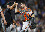 San Francisco Giants shortstop Donovan Solano, left, celebrates with catcher Buster Posey after the team's baseball game against the Colorado Rockies on Saturday, Aug. 3, 2019, in Denver. The Giants won 6-5. (AP Photo/David Zalubowski)