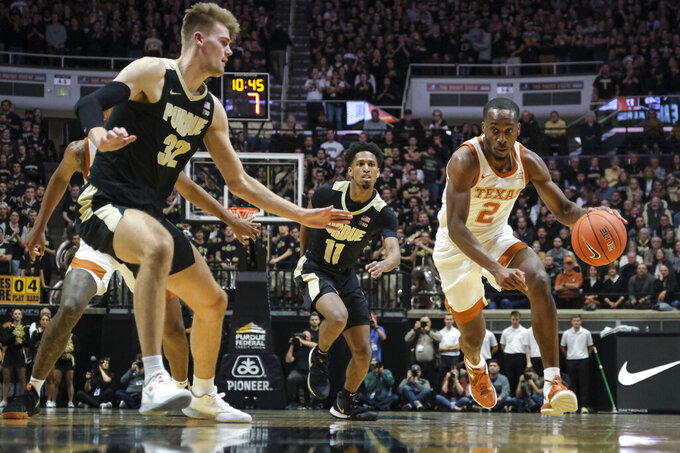 Texas guard Matt Coleman III (2) drives around Purdue center Matt Haarms (32) in the first half of an NCAA college basketball game in West Lafayette, Ind., Saturday, Nov. 9, 2019. (AP Photo/AJ Mast)