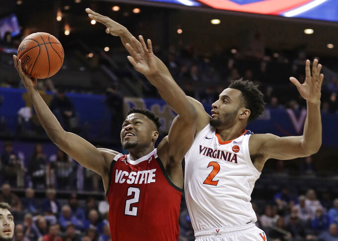 North Carolina State's Torin Dorn, left, drives against Virginia's Braxton Key, right, during the first half of an NCAA college basketball game in the Atlantic Coast Conference tournament in Charlotte, N.C., Thursday, March 14, 2019. (AP Photo/Nell Redmond)