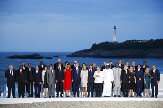 Group of Seven leader and guests pose for the G7 family photo Sunday, Aug. 25, 2019 in Biarritz. A top Iranian official paid an unannounced visit Sunday to the G-7 summit and headed straight to the buildings where leaders of the world's major democracies have been debating how to handle the country's nuclear ambitions. (AP Photo/Francois Mori)
