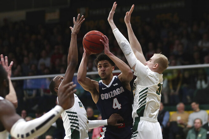 Gonzaga guard Ryan Woolridge (4) is defended by San Francisco center Jonas Visser (31) and Khalil Shabazz (1) during the first half of an NCAA college basketball game in San Francisco, Saturday, Feb. 1, 2020. (AP Photo/Jed Jacobsohn)