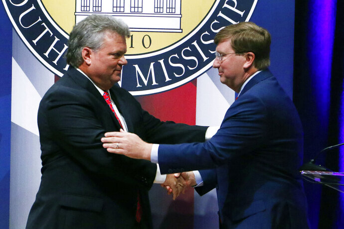 Democratic State Attorney General Jim Hood, left and Republican Lt. Gov. Tate Reeves, right, shake hands at the conclusion of their first televised gubernatorial debate at the University of Southern Mississippi in Hattiesburg, Miss., Thursday, Oct. 10, 2019. (AP Photo/Rogelio V. Solis)