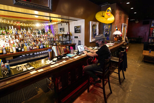 Michael Neff, co-owner of the Cottonmouth Club, works on a computer while sitting at the bar Tuesday, June 23, 2020, in Houston. Neff closed his downtown bar because of concerns within the industry as the number COVID-19 case continues to rise in Houston. (AP Photo/David J. Phillip)