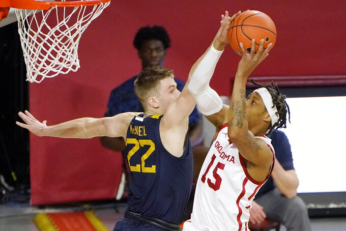 Oklahoma guard Alondes Williams (15) shoots as West Virginia guard Sean McNeil (22) defense in the first half of an NCAA college basketball game Saturday, Jan. 2, 2021, in Norman, Okla. (AP Photo/Sue Ogrocki)