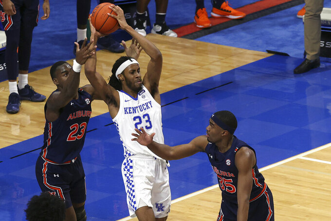 Kentucky's Isaiah Jackson (23) looks for a teammate between Auburn's Jaylin Williams, left, and Devan Cambridge (35) during the second half of an NCAA college basketball game in Lexington, Ky., Saturday, Feb. 13, 2021. Kentucky won 82-80. (AP Photo/James Crisp)