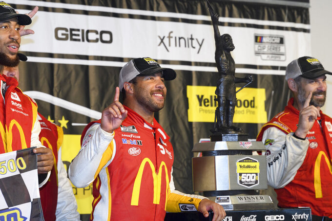 Bubba Wallace, center, stands next to the trophy with teammates after winning a NASCAR Cup series auto race Monday, Oct. 4, 2021, in Talladega, Ala. The race was stopped mid-race due to rain. (AP Photo/John Amis)
