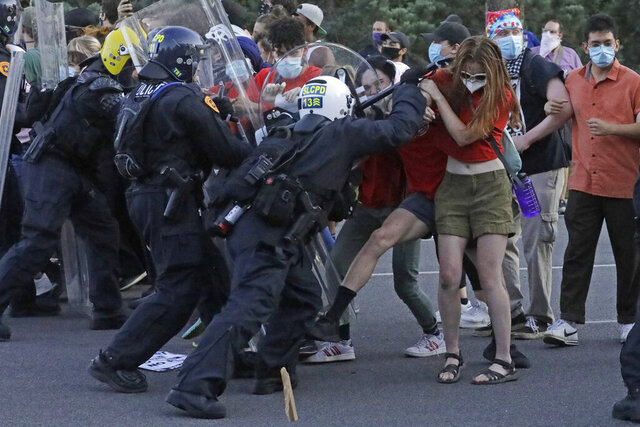 Protesters clash with police officers near the district attorney's office Thursday, July 9, 2020, in Salt Lake City. Two police officers in Utah were cleared earlier Thursday in the death of Bernardo Palacios-Carbajal, an armed man shot at more than 30 times as he ran from police, a decision that prompted his grieving family to heighten their calls for systematic changes to law enforcement. (AP Photo/Rick Bowmer)