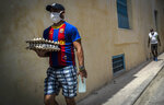 A man wearing a mask as a precaution against the spread of the new coronavirus, and a Barcelona soccer club jersey walks with a package of eggs down the street in Havana, Cuba, Thursday, June 11, 2020. Cuban authorities are requiring the use of masks for anyone outside their homes. (AP Photo/Ramon Espinosa)