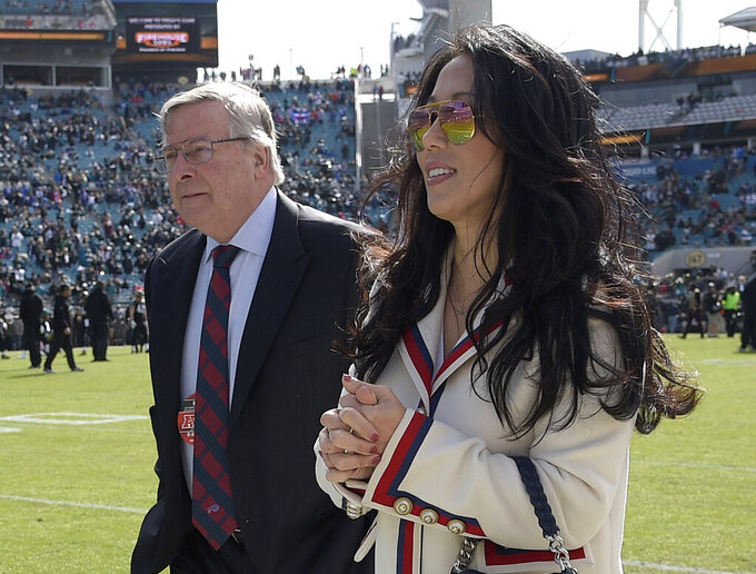 "FILE - In this Jan. 7, 2018, file photo, Buffalo Bills owners Terry and Kim Pegula walk on the sideline before an NFL wild-card playoff football game against the Jacksonville Jaguars in Jacksonville, Fla. Pegula Sports and Entertainment, the parent company that owns the NFL Buffalo Bills and NHL Sabres is experiencing a major shake-up following the departures of three top executives.  PSE CEO and president Kim Pegula says the changes come after she had been ""continuously evaluating our organizations"" since taking over her current title in May. Pegula remains confident in the company's leaders and says the positions will be filled as deemed necessary. (AP Photo/Phelan M. Ebenhack, File)"