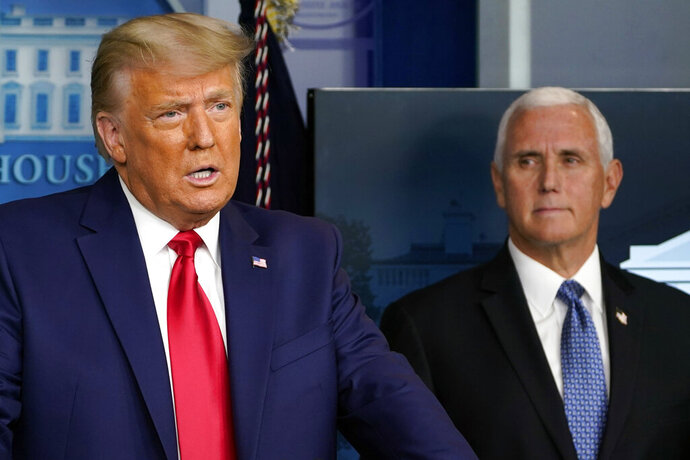 FILE - In this Nov. 24, 2020, file photo President Donald Trump speaks in the press briefing room as Vice President Mike Pence listens in Washington. (AP Photo/Susan Walsh, File)