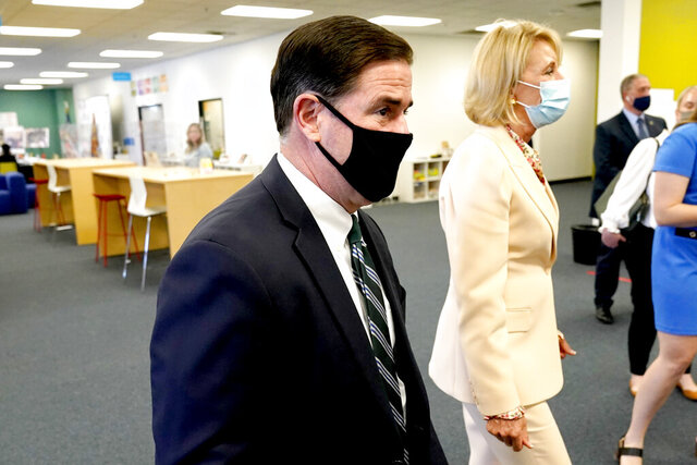 Arizona Gov. Doug Ducey and U.S. Secretary Betsy DeVos take a tour Thursday, Oct. 15, 2020, of the Phoenix International Academy in Phoenix. (AP Photo/Matt York)