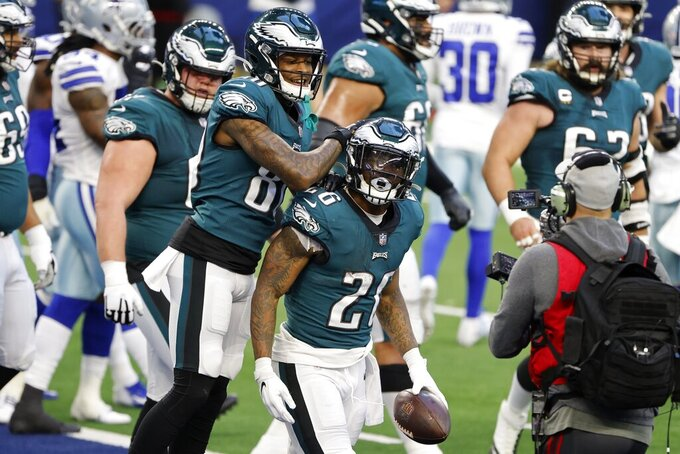 Philadelphia Eagles' Quez Watkins (80) and Miles Sanders (26) celebrate Sanders' touchdown run in the first half of an NFL football game against the Dallas Cowboys in Arlington, Texas, Sunday, Dec. 27. 2020. (AP Photo/Michael Ainsworth)