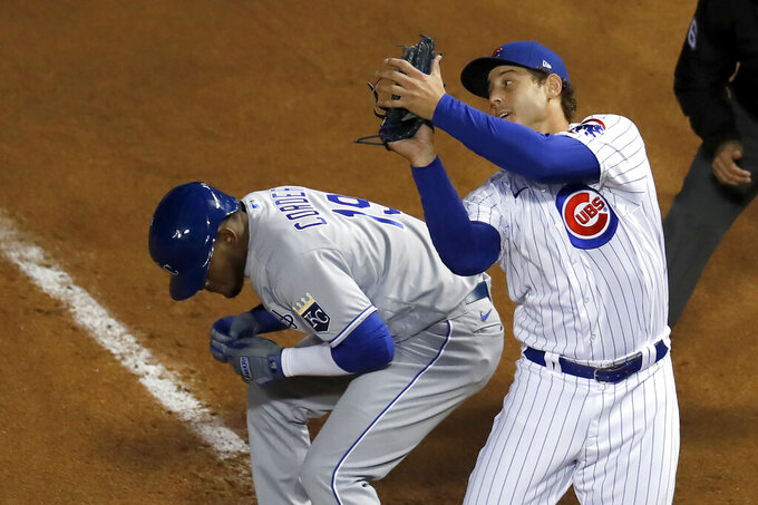 FILE - In this Aug. 3, 2020, file photo, Chicago Cubs first baseman Anthony Rizzo, right, catches a popup by Kansas City Royals' Adalberto Mondesi near Royals' Franchy Cordero, left, on first during the ninth inning of a baseball game in Chicago. The Cubs picked up their $16.5 million option for Rizzo on Saturday, Oct. 31, 2020, bringing back the popular first baseman after he struggled during the pandemic-shortened season. (AP Photo/Charles Rex Arbogast, File)